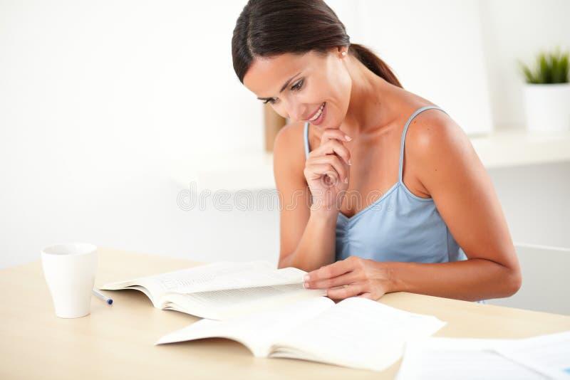 Mulher bonita que lê um livro em sua mesa imagem de stock royalty free