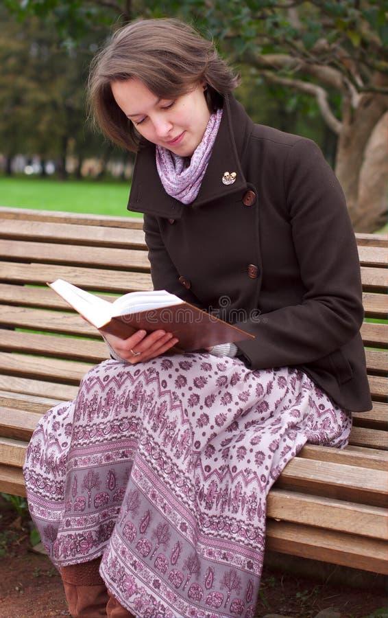 Mulher bonita que lê um livro em um banco imagens de stock