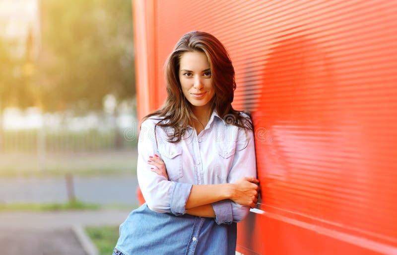 Mulher bonita que levanta contra a parede colorida fotos de stock