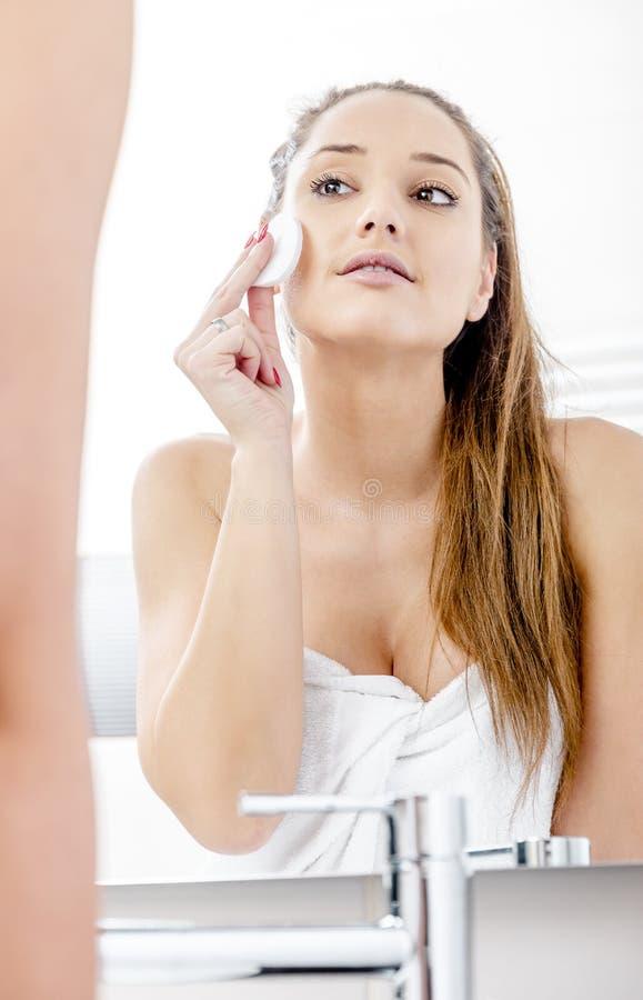 Mulher bonita que limpa sua cara fotos de stock