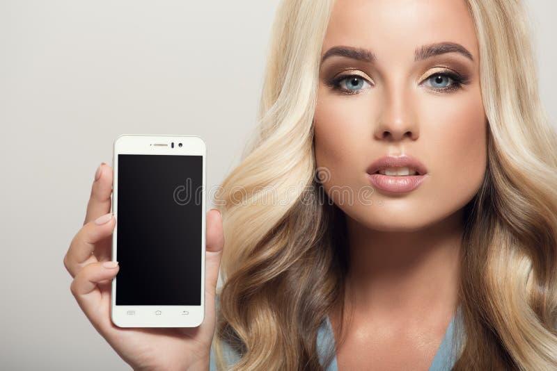 Mulher bonita que mantém o smartphone disponivel Exposição do molde Cl fotografia de stock royalty free