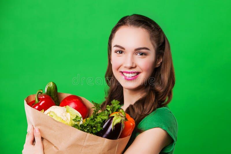 Mulher bonita que mantém um saco de mantimento completo do alimento fresco e saudável No fundo verde imagem de stock royalty free