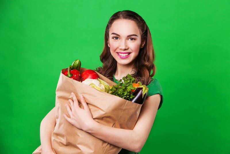 Mulher bonita que mantém um saco de mantimento completo do alimento fresco e saudável olhando a câmera foto de stock
