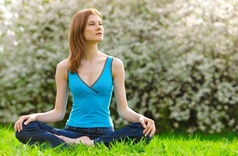 Mulher bonita que meditating ao ar livre foto de stock