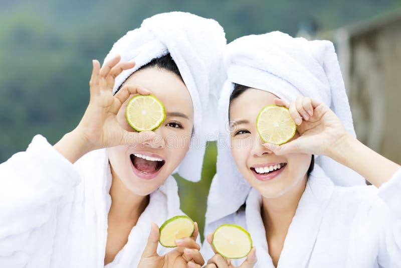 Mulher bonita que mostra o limão fresco nos termas foto de stock royalty free