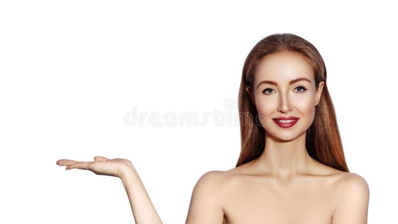 Mulher bonita que mostra o produto Menina com composição da forma que aponta ao lado Apresentando seu produto de beleza imagens de stock royalty free