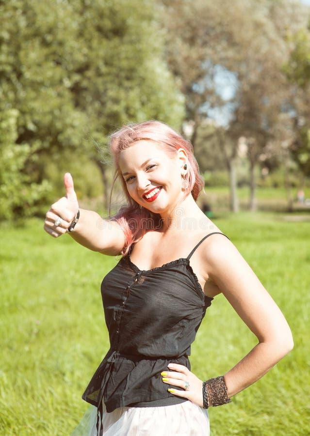 A mulher bonita que mostra os polegares levanta exterior fotografia de stock