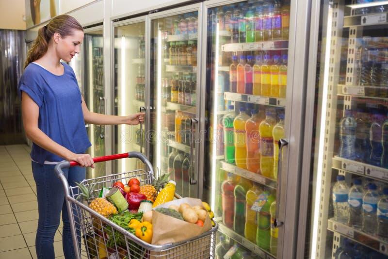 Mulher bonita que olha a câmera e que toma o produto no refrigerador fotografia de stock royalty free