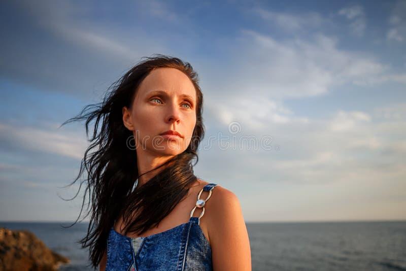 Mulher bonita que olha na distância no por do sol contra o céu fotografia de stock
