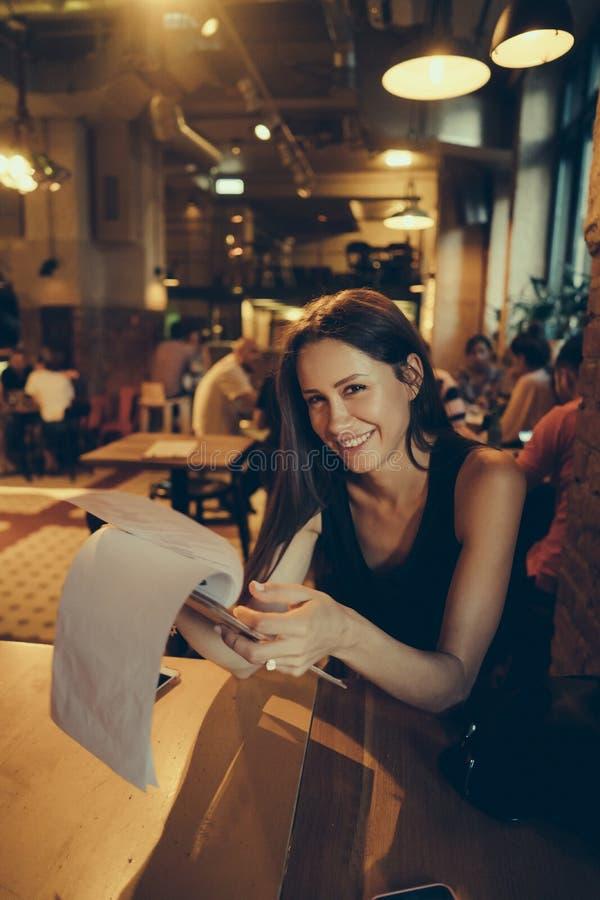 Mulher bonita que olha o menu no café fotografia de stock royalty free