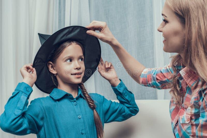 Mulher bonita que põe o chapéu da bruxa sobre a menina imagem de stock royalty free