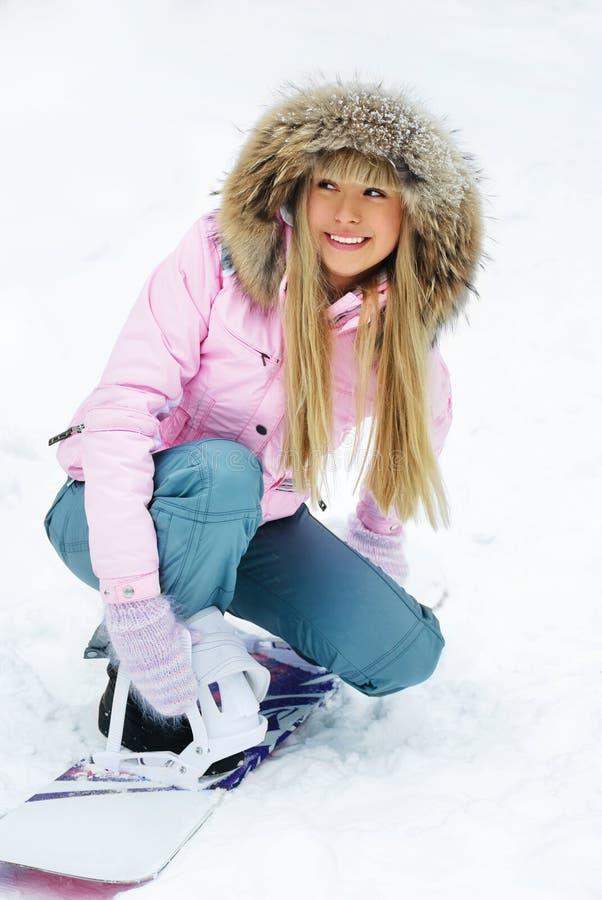 Mulher bonita que põr sobre um snowboard fotografia de stock