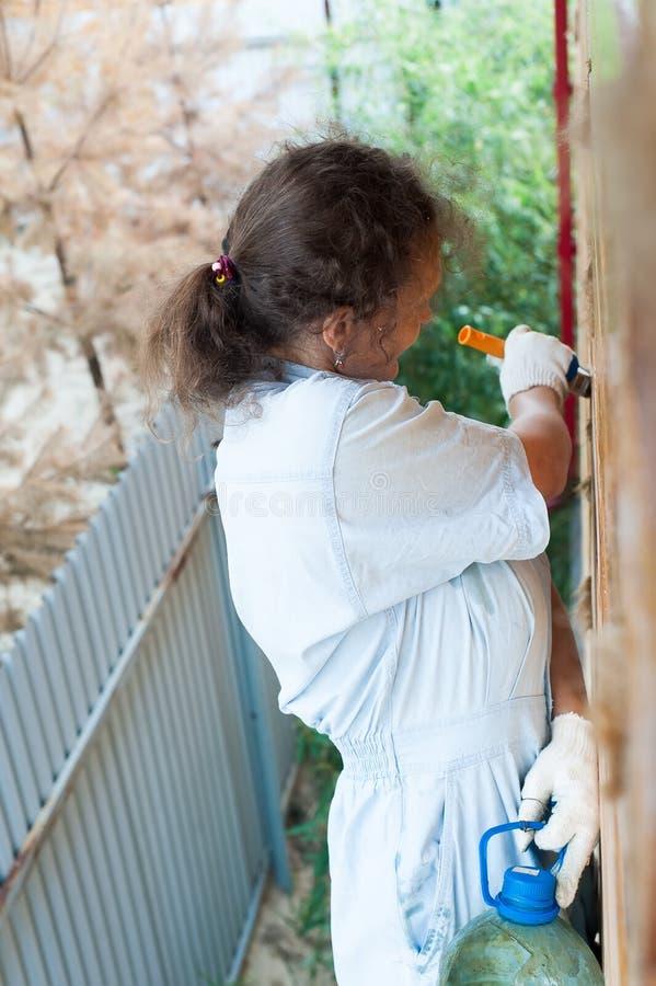 Mulher bonita que pinta sua casa imagem de stock