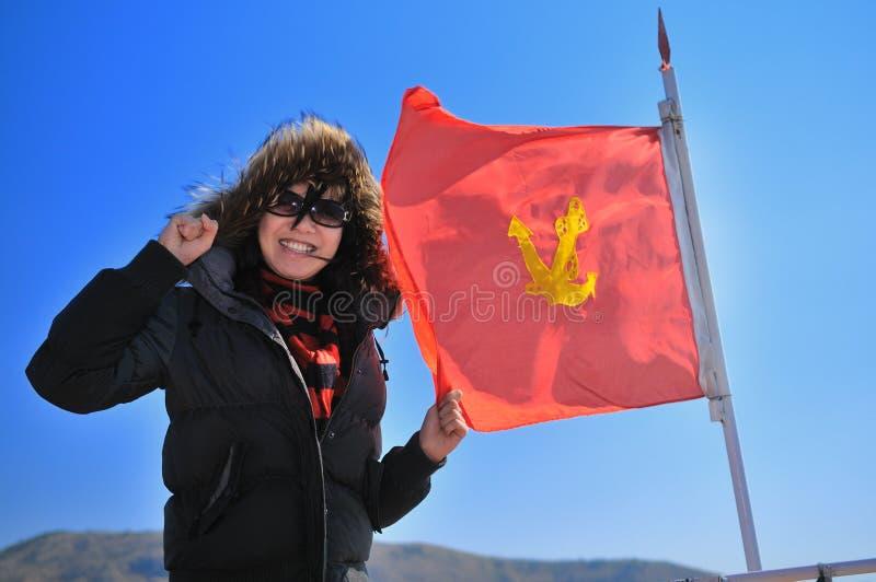 Mulher bonita que prende uma bandeira vermelha imagens de stock royalty free