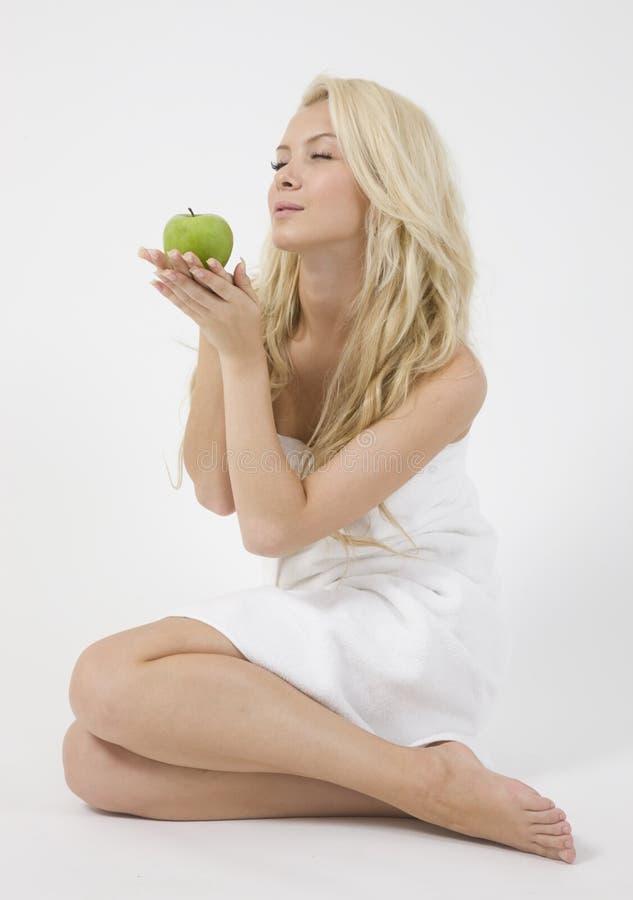 Mulher bonita que prende uma maçã fotografia de stock royalty free
