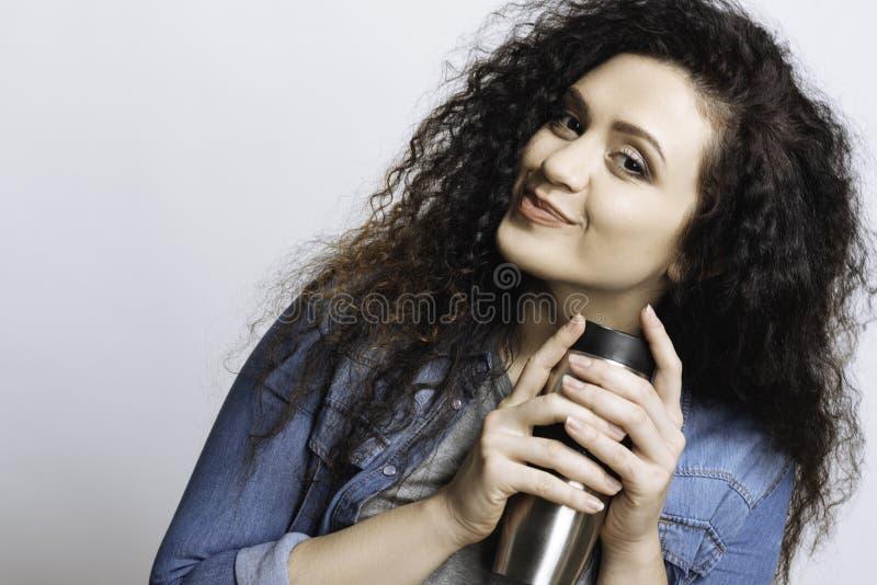 Mulher bonita que propõe a bebida morna foto de stock