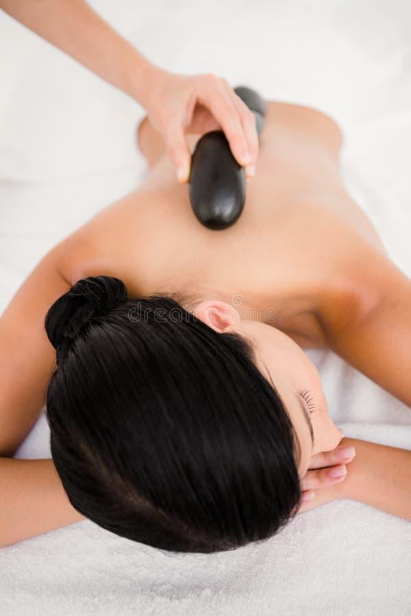 Mulher bonita que recebe uma massagem de pedra quente imagem de stock