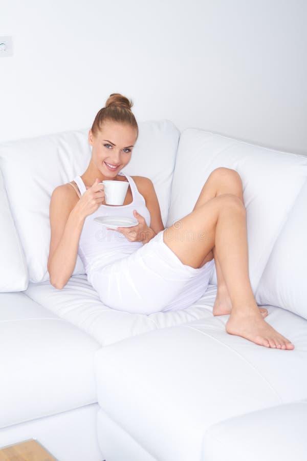 Mulher bonita que relaxa em casa com café fotos de stock royalty free