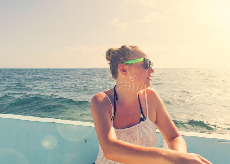 Mulher bonita que relaxa em um barco foto de stock