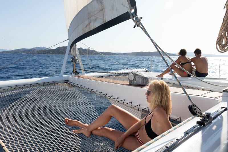 Mulher bonita que relaxa em um ver?o que navega o cruzeiro, encontrando-se e tomando sol na rede do catamar? luxuoso que navega a imagem de stock royalty free