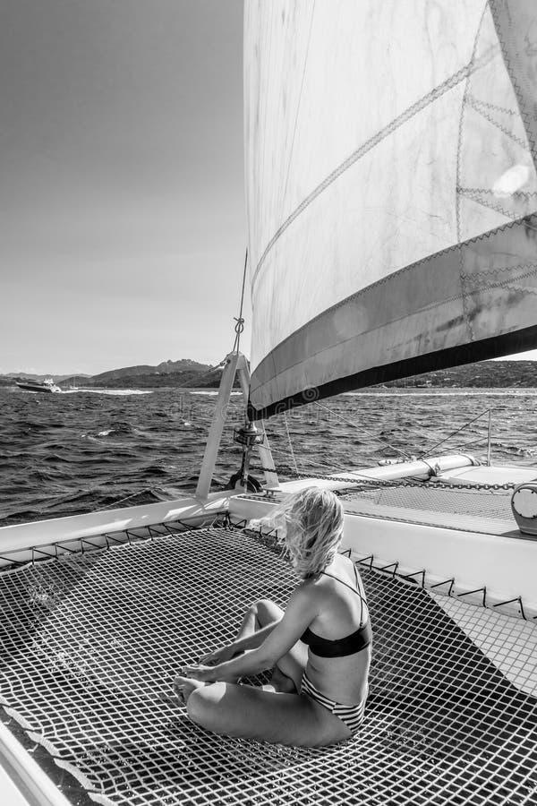 Mulher bonita que relaxa em um ver?o que navega o cruzeiro, sentando-se e tomando sol na rede da naviga??o luxuosa do catamar? fotografia de stock royalty free