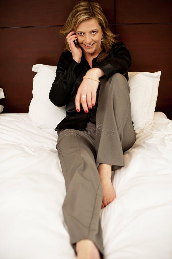 Mulher bonita que relaxa na cama e que fala no telefone fotografia de stock royalty free