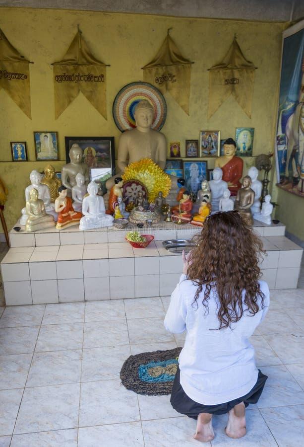 Mulher bonita bonita que reza perto do altar budista fotos de stock