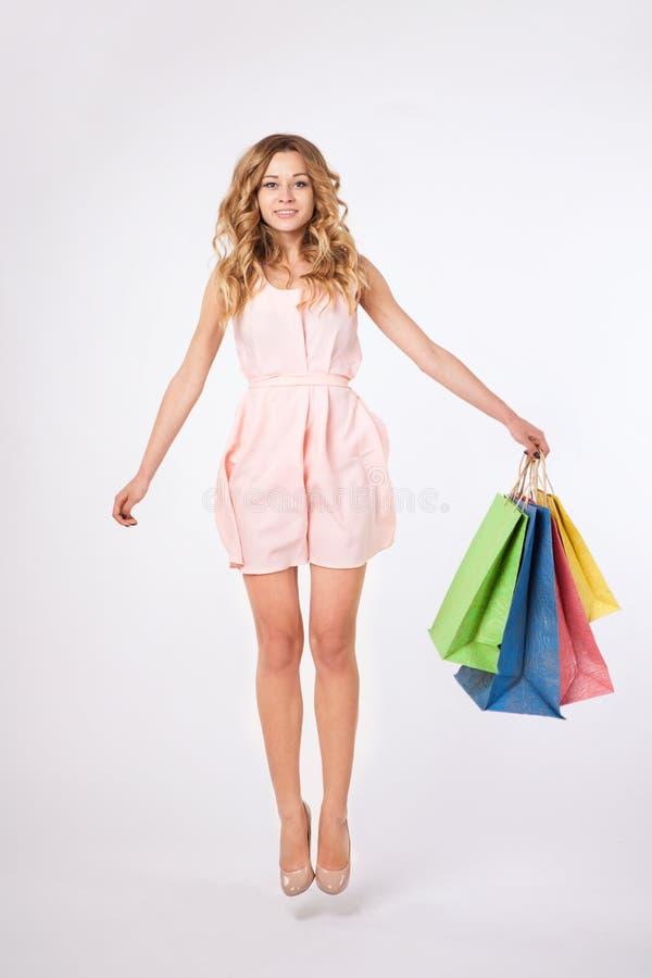 Mulher bonita que salta e que guarda sacos de compras fotos de stock