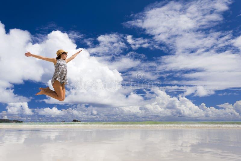 Mulher bonita que salta na praia foto de stock royalty free