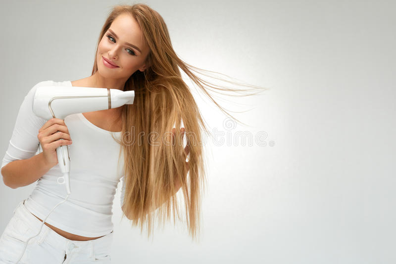 Mulher bonita que seca o cabelo reto usando o secador hairdressing imagem de stock royalty free