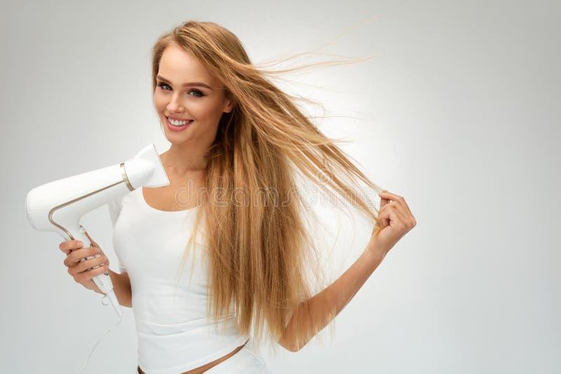 Mulher bonita que seca o cabelo reto usando o secador hairdressing fotografia de stock