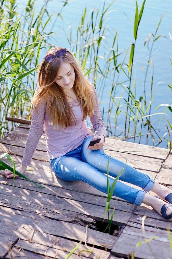 Mulher bonita que senta-se em um cais no lago fotografia de stock