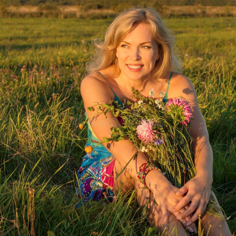 Mulher bonita que senta-se em um campo com flores e sorrisos imagem de stock royalty free