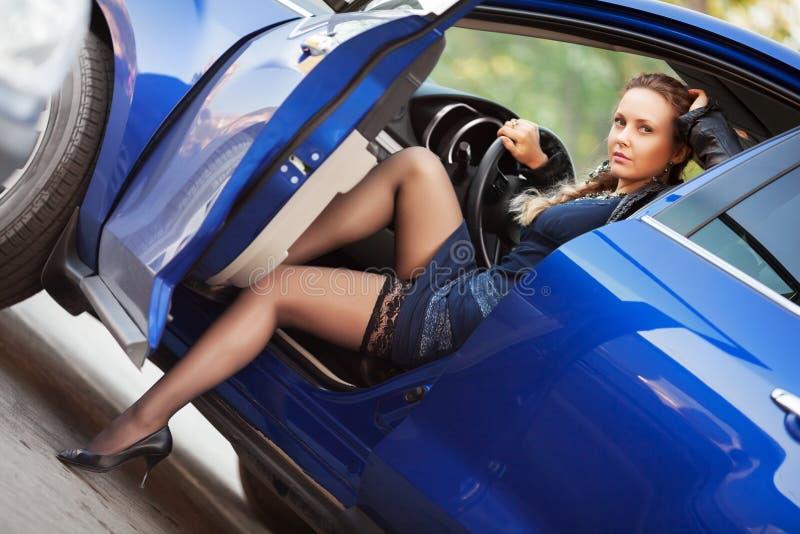 Mulher bonita que senta-se em um carro foto de stock royalty free