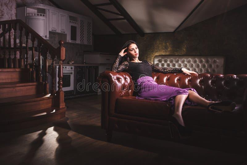 Mulher bonita que senta-se em um sofá de couro do vintage imagens de stock