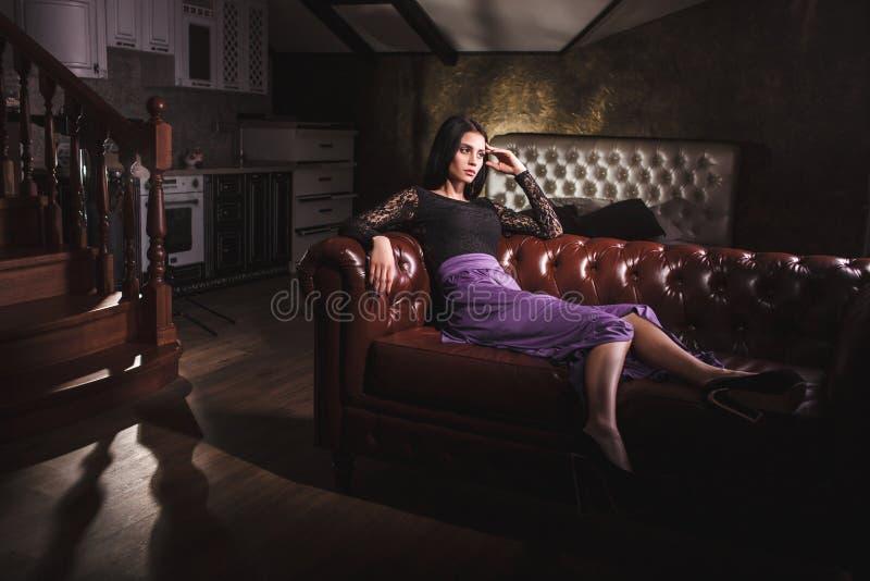 Mulher bonita que senta-se em um sofá de couro do vintage foto de stock