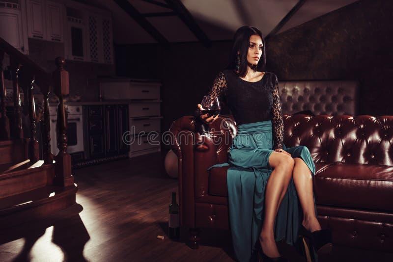 Mulher bonita que senta-se em um sofá de couro do vintage fotos de stock royalty free