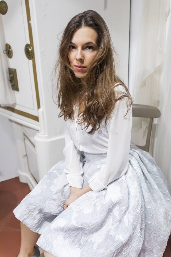 Mulher bonita que senta-se em uma cadeira em um shopping que espera em uma oficina foto de stock