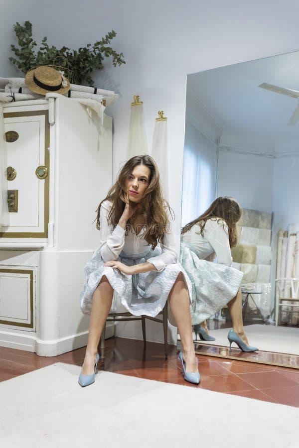 Mulher bonita que senta-se em uma cadeira em um shopping que espera em uma oficina fotos de stock