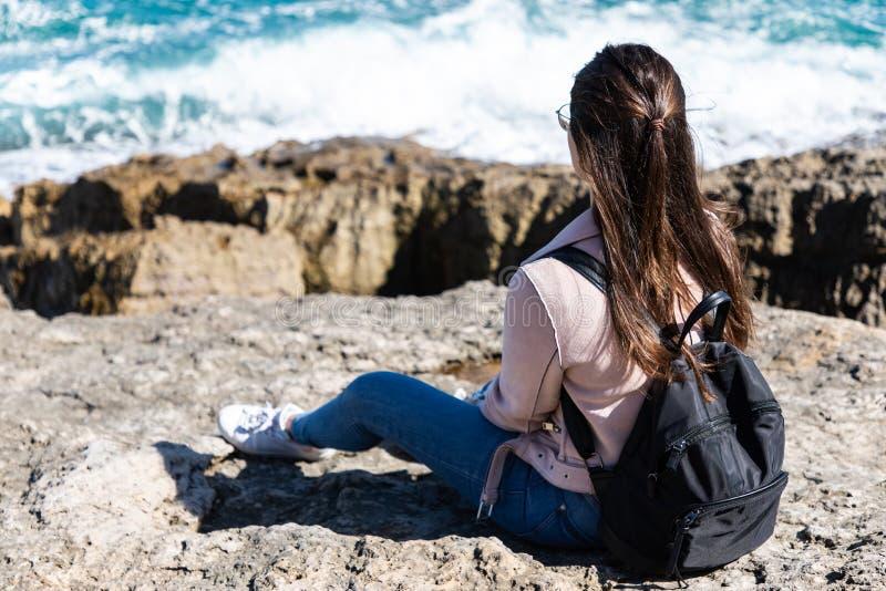 Mulher bonita que senta-se na costa que olha as ondas fotos de stock royalty free