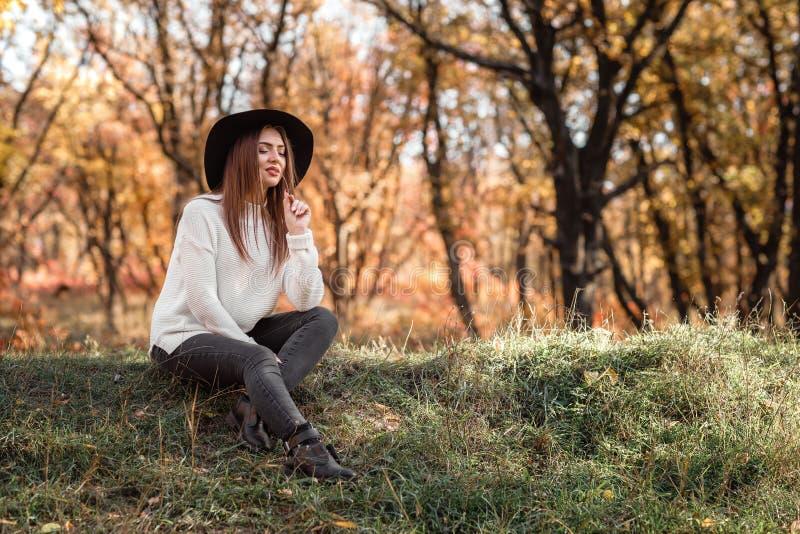 Mulher bonita que senta-se na grama no dia ensolarado do outono foto de stock royalty free