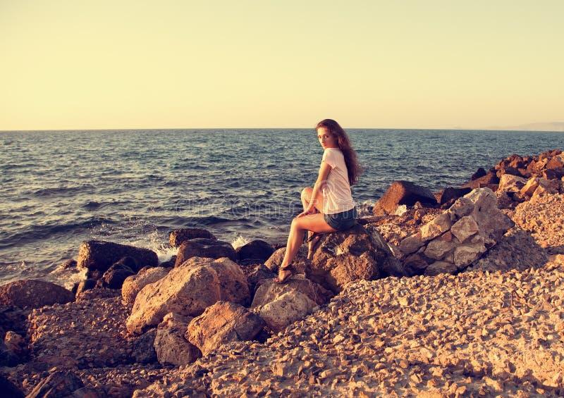 A mulher bonita que senta-se na rocha perto do mar azul com relaxa fotografia de stock royalty free