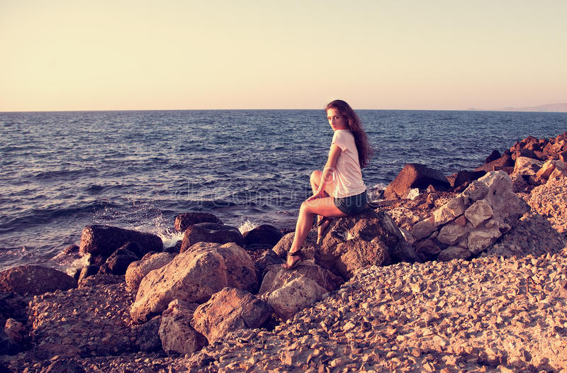Mulher bonita que senta-se na rocha perto dos wi azuis do mar e do céu imagem de stock