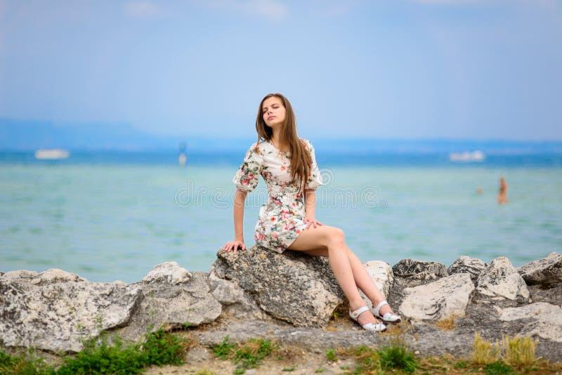 Mulher bonita que senta-se na rocha sobre o mar fotos de stock royalty free