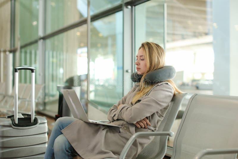 Mulher bonita que senta-se na sala de espera com o portátil perto do valise, usando o descanso do pescoço fotos de stock