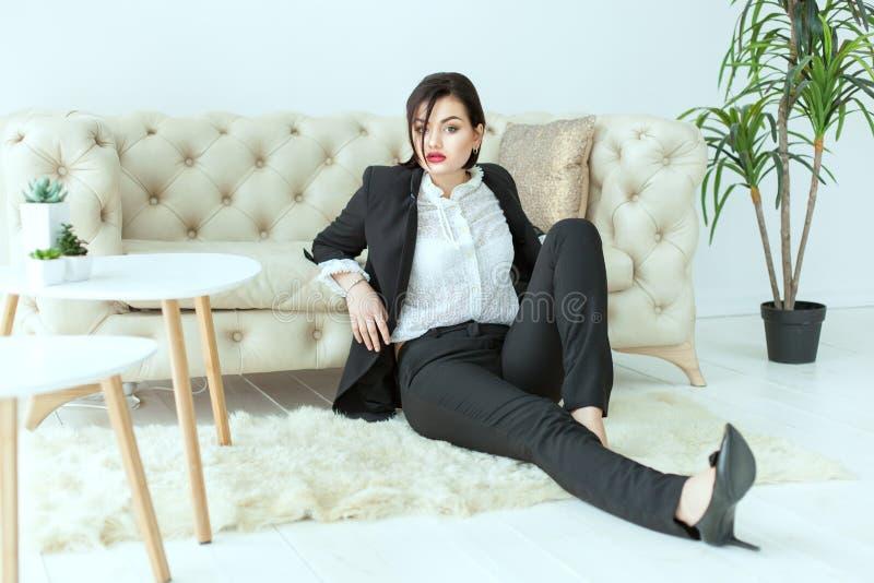Mulher bonita que senta-se no assoalho fotografia de stock royalty free