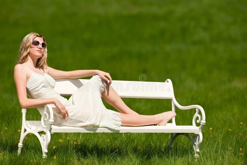Mulher bonita que senta-se no banco branco imagem de stock