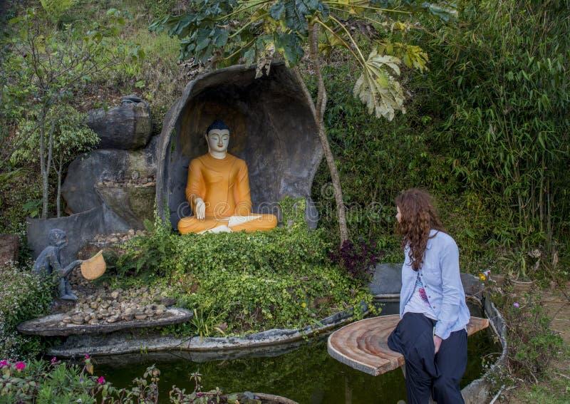 Mulher bonita bonita que senta-se no banco perto do altar budista imagens de stock royalty free