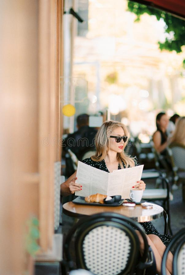 Mulher bonita que senta-se no caf? imagens de stock royalty free