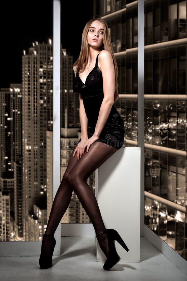 Mulher bonita que senta-se no indicador e na vista imagem de stock